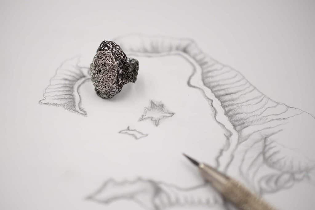 silver adjustable oval ring on a sketch of the island of santorini