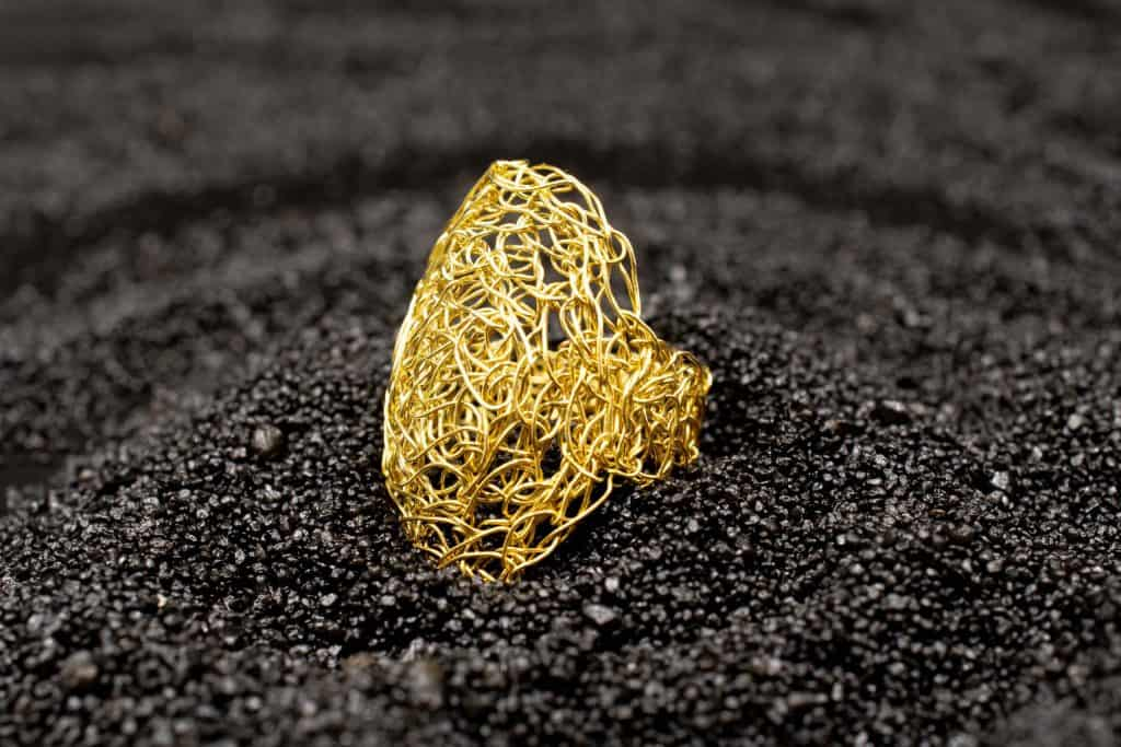 detail of gold oval ring on lava background