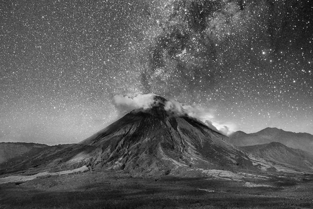 volcano surrounded by clouds on a sky full of stars