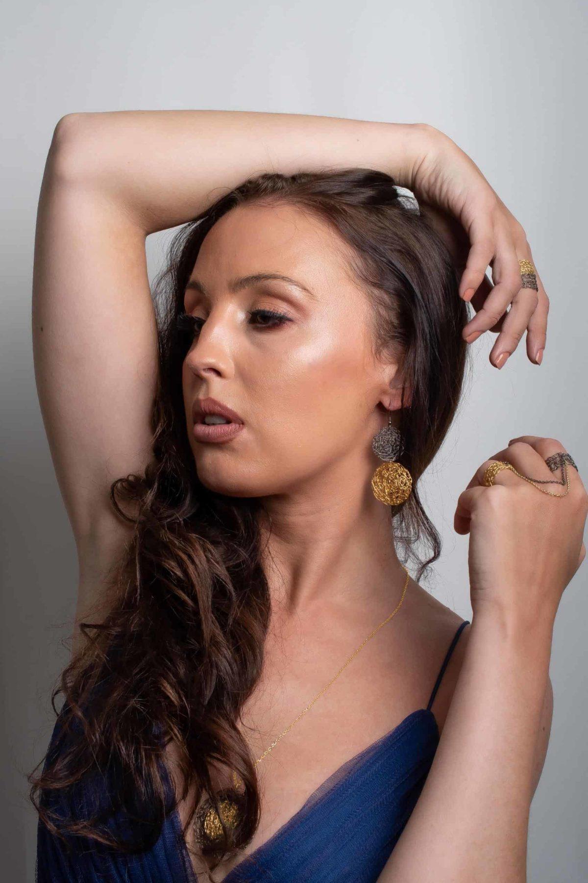 White model wearing gold statement earrings