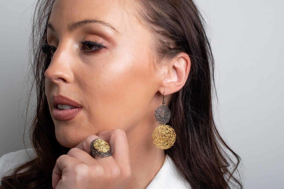white model wearing statement earrings in gold