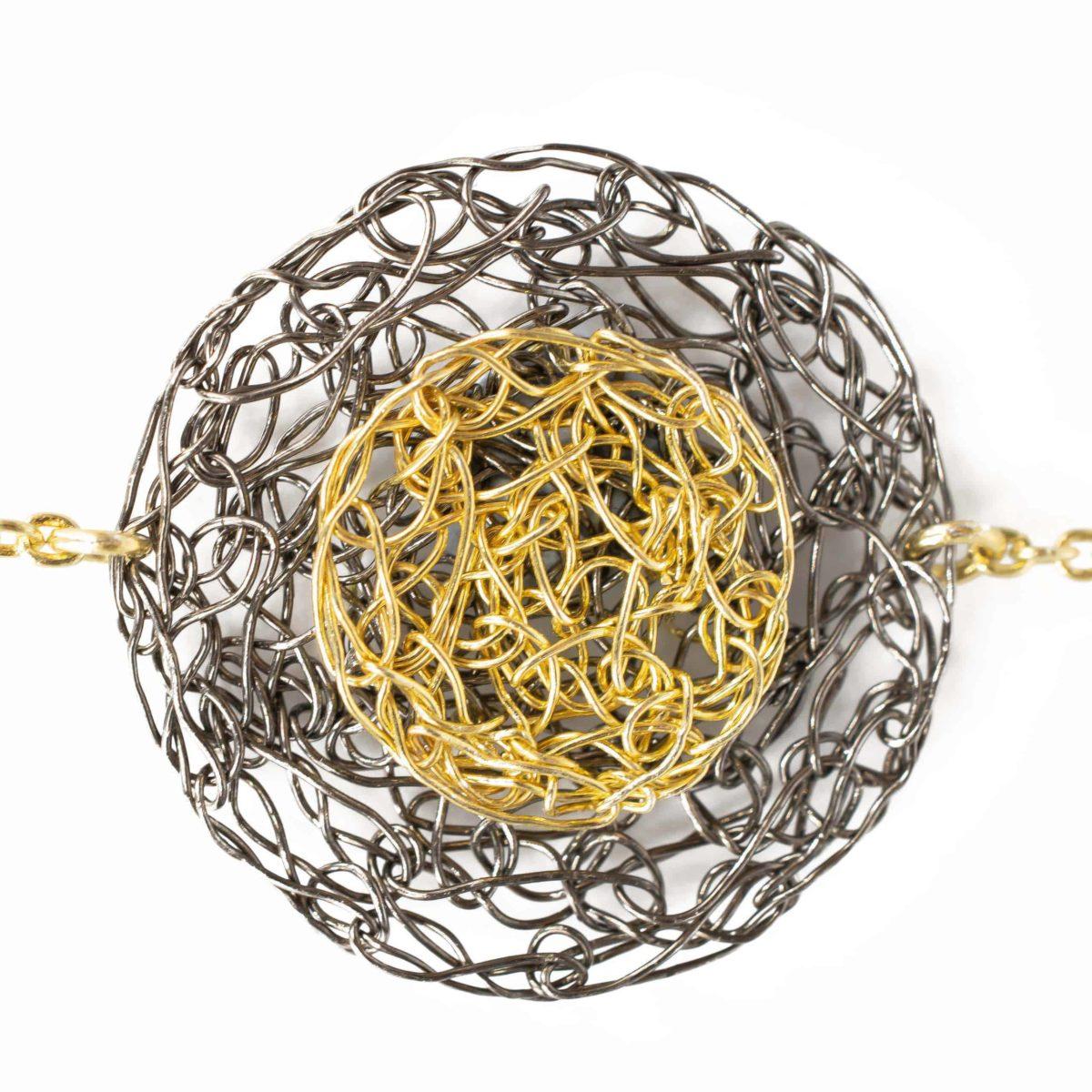 detail of charm bracelet in gold