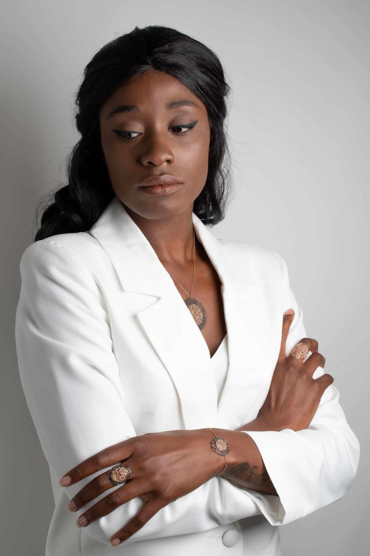 model with white clothes wearing rose gold jewelry