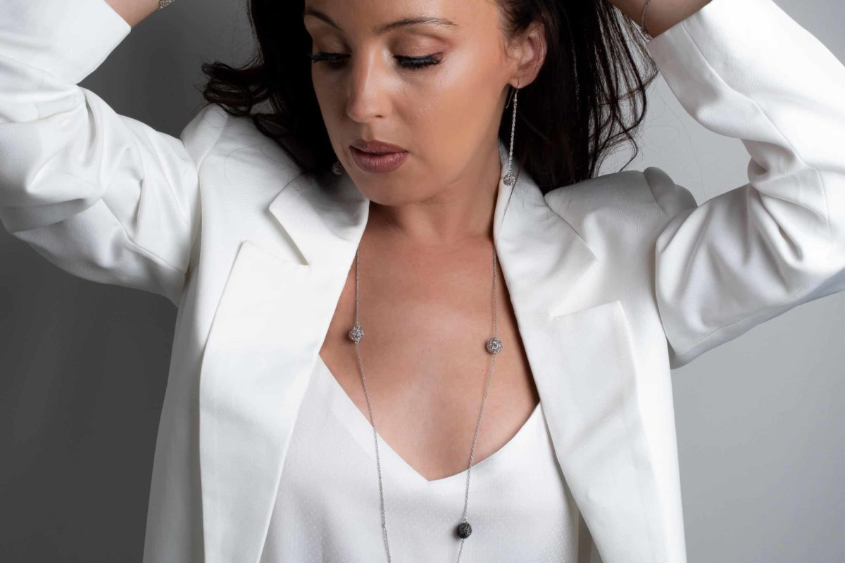 white model displaying a long pendant necklace