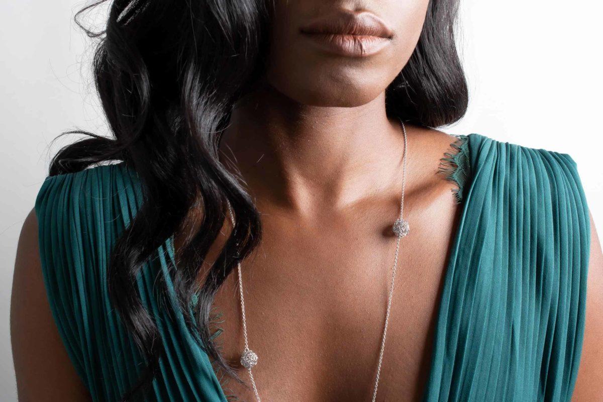 model wearing long silver pendant necklace