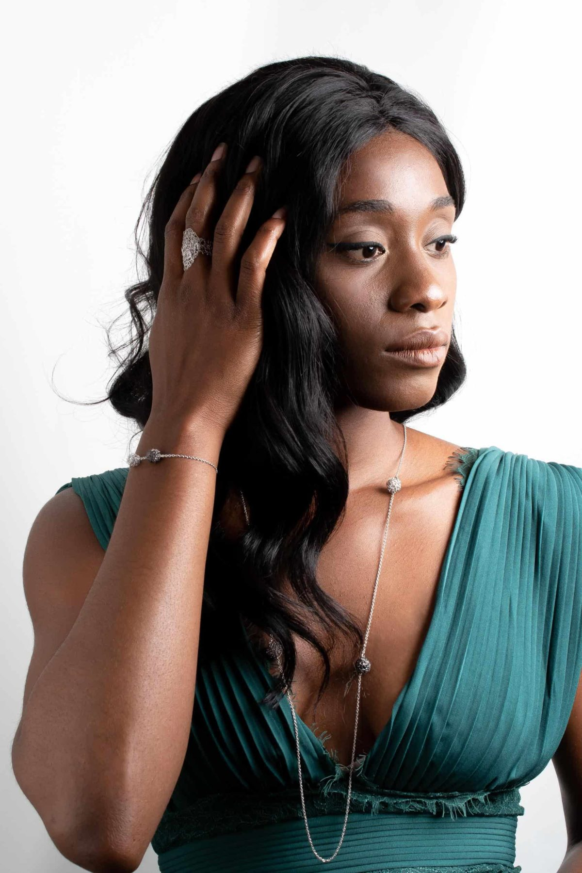 black model displaying a long pendant necklace