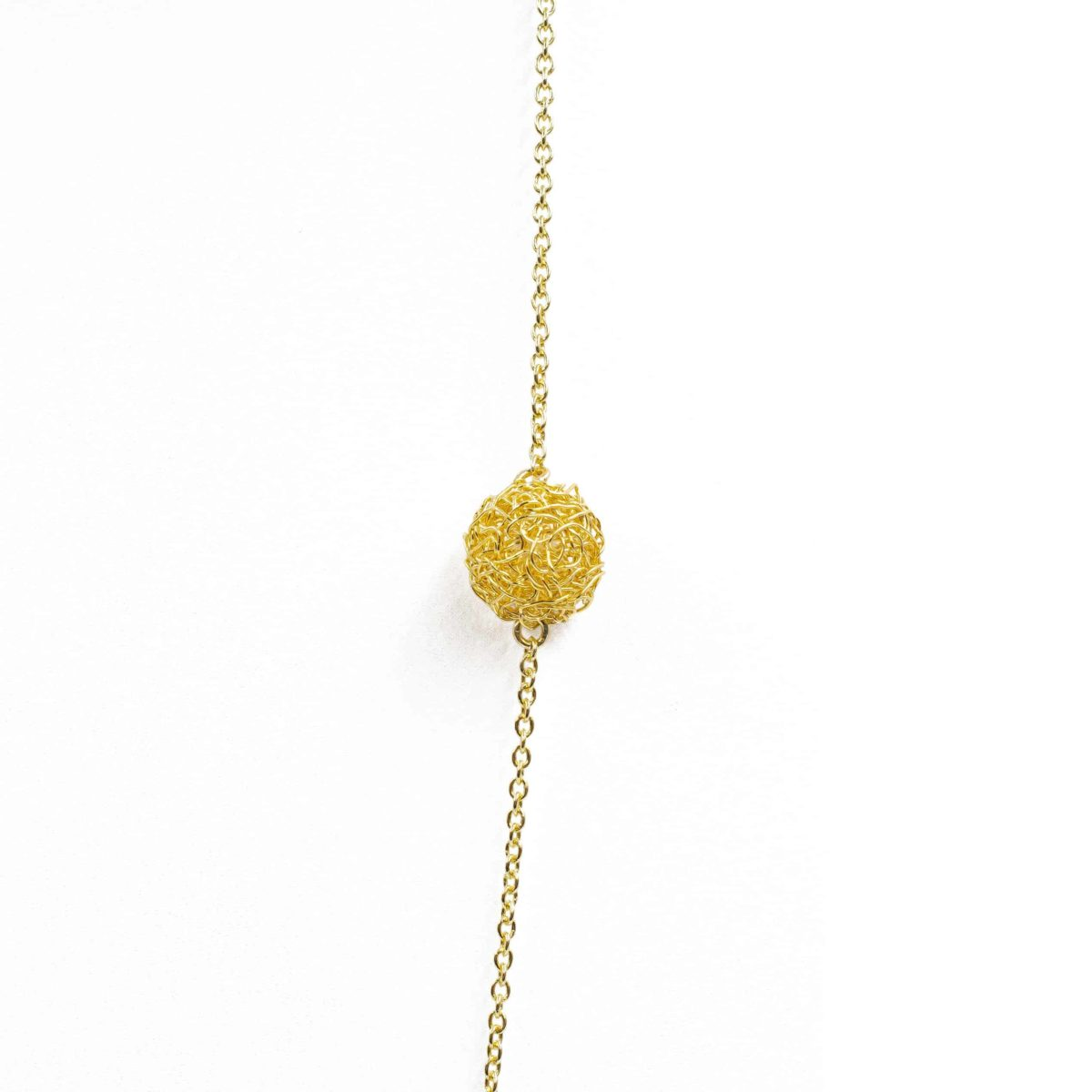 detail of gold sphere in long pendant necklace