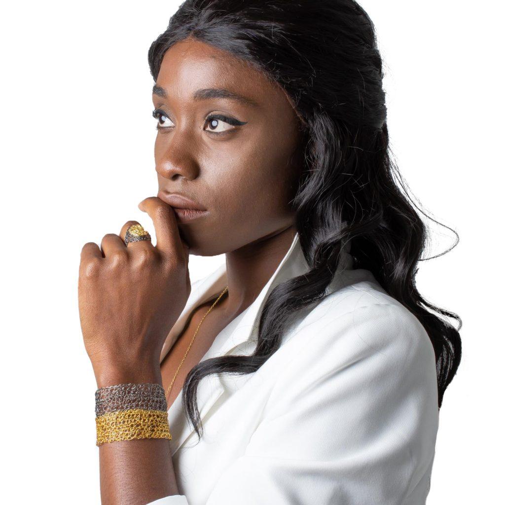 Black model wearing a gold bangle bracelet and an adjustable ring